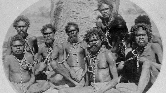 Aboriginal men in chains seated around a tree. (Photo Credit: © Courtesy of State Library of Western Australia)